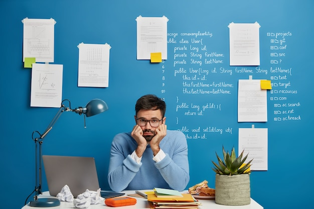 Verveelde mannelijke undergraduate faalt of heeft een probleem tijdens het werk