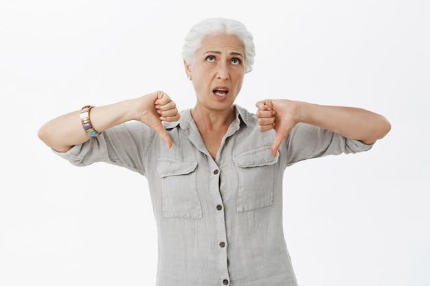 Verveelde sceptische oudere vrouw die ontevreden kijkt, duimen naar beneden toont in afkeer en ogen oprolt