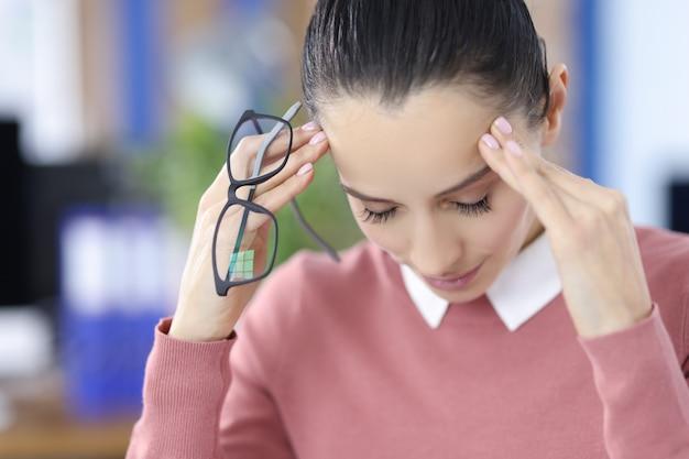 Verveelde slaperige zakenvrouw die half in slaap zit op de werkplek luie vrouw hoofdpijn en vermoeidheid in