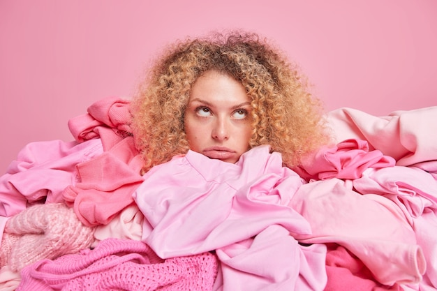 Verveelde trieste jonge vrouw met krullend borstelig haar poseert rond hopen kleding gericht boven geïsoleerd over roze muur. rommelige vrouwelijke kledingkast. recycling van stoffen en textiel hergebruik concept.