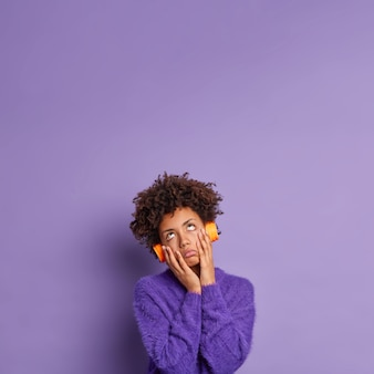 Verveelde vermoeiende afro-amerikaanse vrouw houdt handen op de wangen gefocust boven draagt een koptelefoon om naar favoriete muziek te luisteren, gekleed in een casual trui