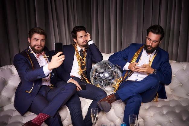 Verveelde vrienden met mobiele telefoon op nieuwjaarsfeest