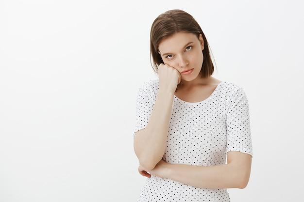 Verveelde vrouw die terughoudend kijkt, naar een zwak verhaal luistert, zich geïrriteerd voelt