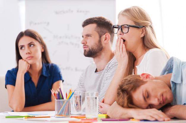 Vervelende presentatie. groep jonge zakenmensen in slimme vrijetijdskleding die er verveeld uitzien terwijl ze samen aan tafel zitten en wegkijken