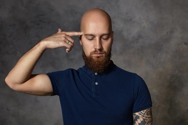 Verveling, vermoeidheid en depressie concept. geïsoleerde schot van depressieve, ongelukkige blanke man met dikke baard die zijn vinger naar zijn slaap houdt en ogen sluit alsof hij schiet, zich gestrest voelt