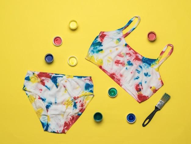Verven en lingerie in de stijl van tie dye op een gele achtergrond. gekleurd ondergoed in huis.