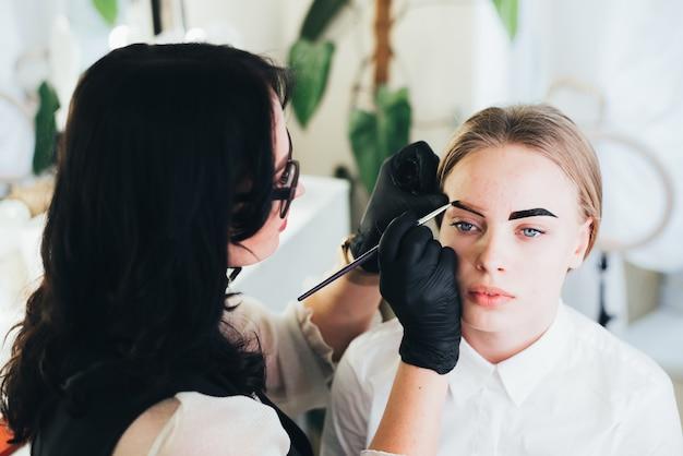 Verven en vormgeven van wenkbrauwen. meisje in een schoonheidssalon.