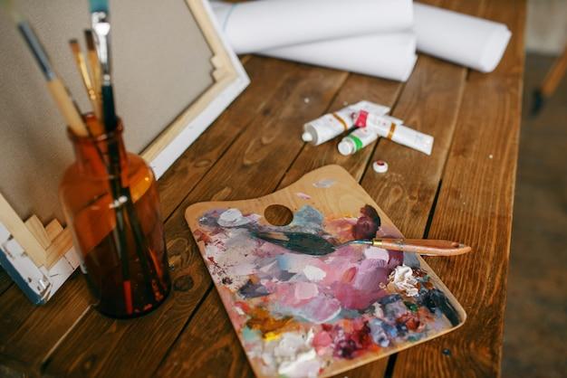 Verven op palet, penseel in fles, canvas, niemand. schildergereedschap op tafel in kunstatelier, apparatuur op kunstenaarswerkplek, penseel, creatief atelier of werkplaats
