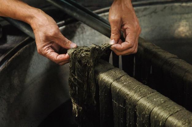 Verven van draden en garens mannelijke handen schilderen de doek in de trog