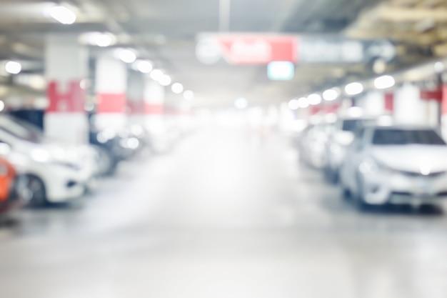 Vervuil de ondergrondse parkeergarage van auto's met licht op gebruik van de uitgangsmanier als achtergrond
