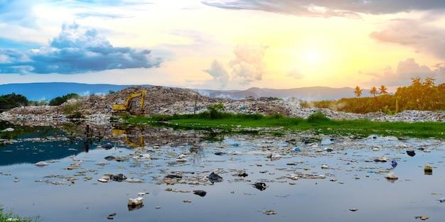 Vervuild water en berg grote vuilnishoop en vervuiling