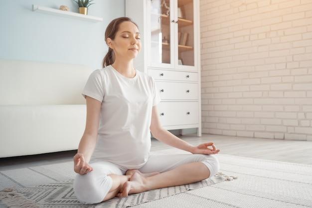 Verwacht dat moeder yoga-oefening doet in het zijaanzicht van de zwangerschap copyspace