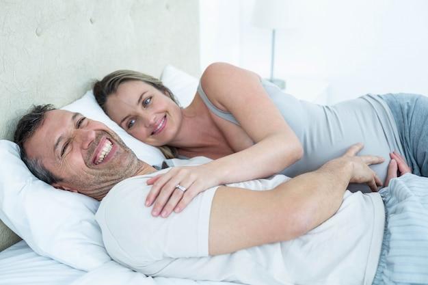 Verwacht paar liggend op bed en chatten in hun slaapkamer
