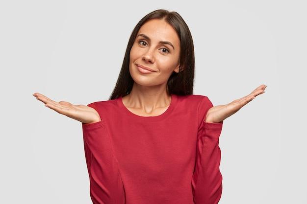 Verward aantrekkelijke brunette jonge vrouw heeft een aantrekkelijke uitstraling, een gebruinde gezonde huid, maakt een twijfelachtig gebaar, voelt zich verbaasd terwijl ze een beslissing neemt, aarzelt wat ze moet kiezen, poseert alleen tegen een witte muur.