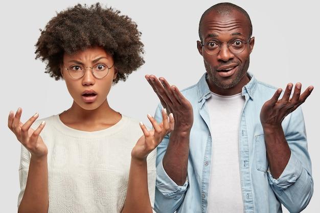 Verward afrikaans amerikaans paargebaar samen met verwarring, ontevreden zijn over de omstandigheden in het hotel waar ze zullen verblijven, hebben geen idee van uitdrukkingen, geïsoleerd over witte muur