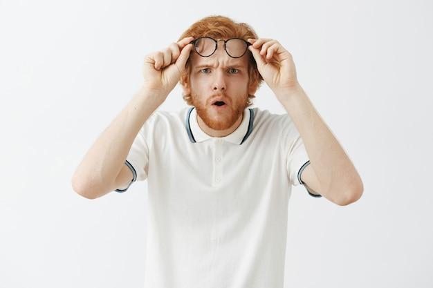 Verward bebaarde roodharige man poseren tegen de witte muur met een bril