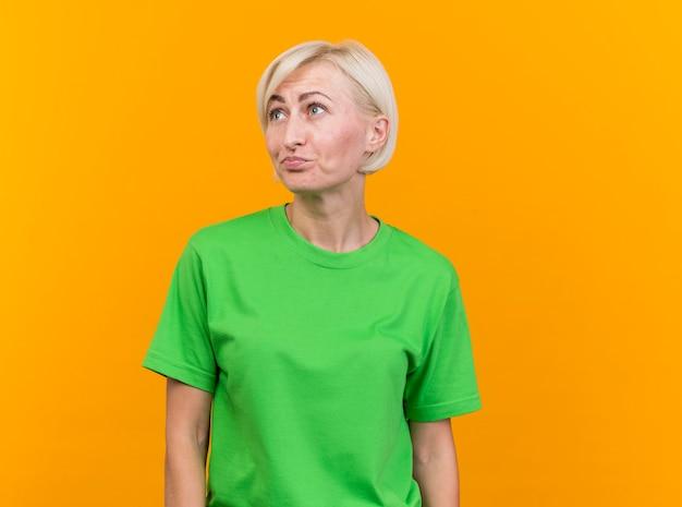 Verward blonde slavische vrouw op middelbare leeftijd die kant bekijkt die op gele achtergrond met exemplaarruimte wordt geïsoleerd