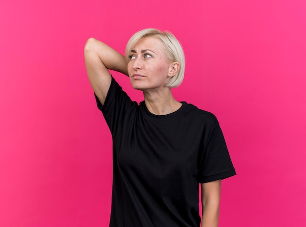 Verward blonde slavische vrouw van middelbare leeftijd die hand achter hoofd houdt die kant bekijkt die op roze muur met exemplaarruimte wordt geïsoleerd