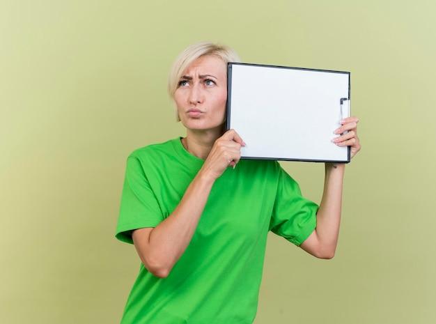 Verward blonde slavische vrouw van middelbare leeftijd met klembord in de buurt van hoofd aanraken van hoofd met het kijken naar kant geïsoleerd op olijfgroene muur met kopie ruimte