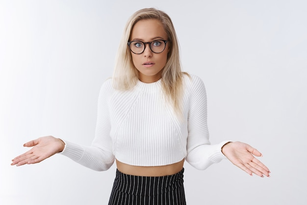 Verward, clueless bezorgde vrouwelijke assistent in glazen bijgesneden trui en rok schouderophalend met de handen zijwaarts open mond in verwarring en frustratie die zich niet bewust en geen idee heeft over de witte muur.