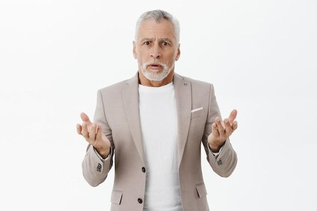 Verward en bezorgde zakenman in pak kijkt verbaasd, kan niet begrijpen wat er gebeurt