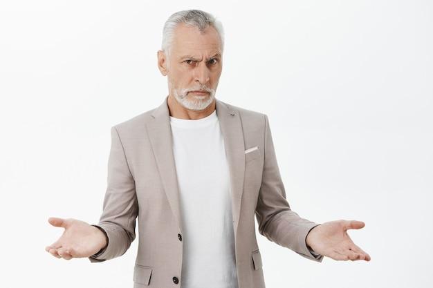 Verward en geen idee van een senior man die zijn handen zijwaarts opheft en er ingewikkeld uitziet