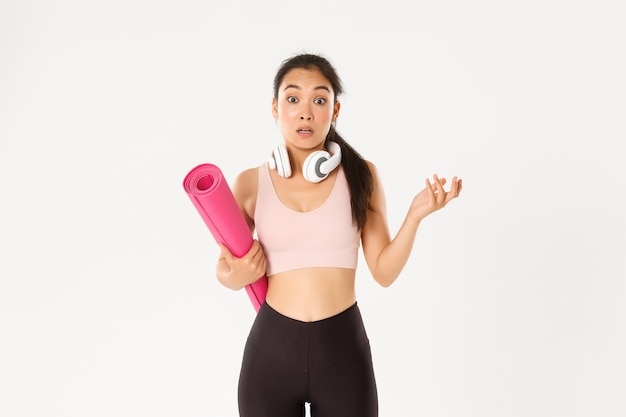 Verward en geschokt aziatisch fitnessmeisje, kan niet begrijpen waarom sportschool gesloten is, rubberen mat vasthoudt en verbaasd naar de camera kijkt,