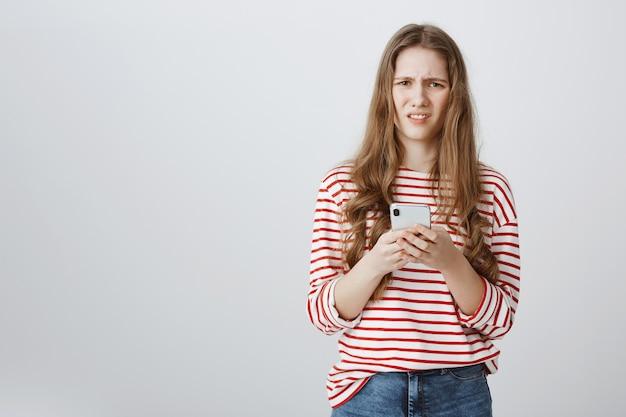 Verward en onrustig meisje fronst en kijkt verbaasd, terwijl ze mobiele telefoon vasthoudt