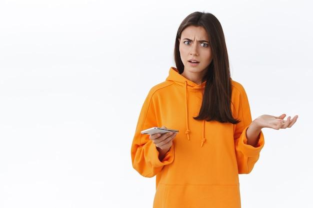 Verward en ontevreden verbaasd jong meisje haalt haar schouders op met zijwaarts gespreide hand, starend naar iemand die klaagt, smartphone vasthoudt, kan de betekenis van het bericht niet begrijpen