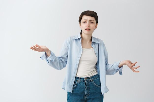 Verward en teleurgesteld meisje dat haar schouders ophaalt en er ingewikkeld uitziet, kan het niet begrijpen
