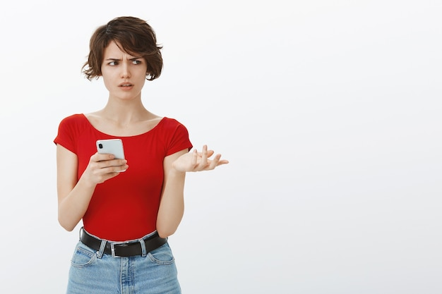 Verward en verbaasd aantrekkelijke vrouw wegkijken ondervraagd, telefoon vasthouden, kan bericht niet begrijpen