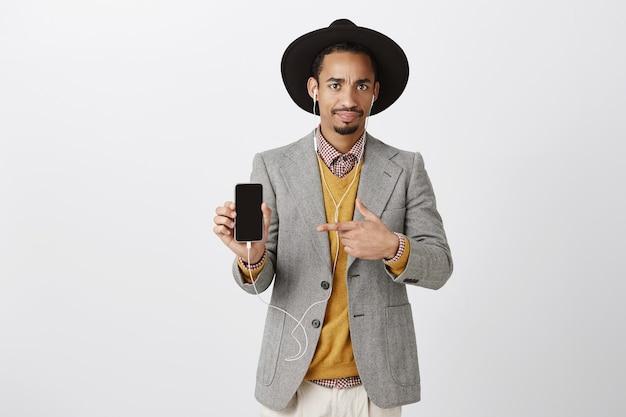 Verward en verbaasd afro-amerikaanse man in pak wijzende vinger op mobiele telefoon met sceptische uitdrukking