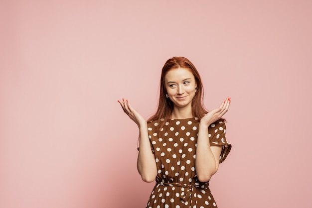 Verward en verbaasd vrouw op een roze muur. een meisje in een mooie bruine jurk toont de emotie van niet begrijpen.