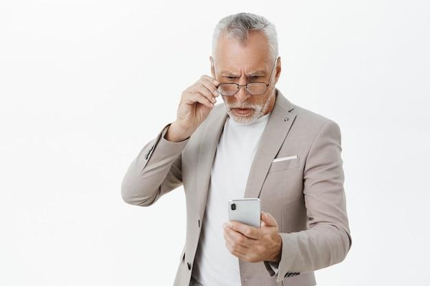 Verward ernstig ogende bejaarde zakenman die het scherm van de mobiele telefoon bekijkt