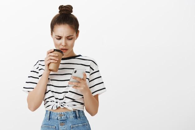 Verward fronsend meisje dat naar het scherm van de mobiele telefoon kijkt terwijl ze een slokje koffie uit de beker maakt