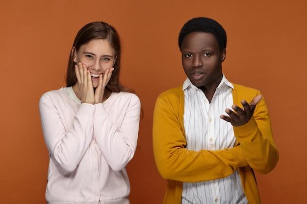 Verward geen idee jonge afro-amerikaanse man gebaart, verlieslatend terwijl mooi positief kaukasisch vrouw hand in hand op haar wangen en gelukkig lachend, opgewonden gevoel