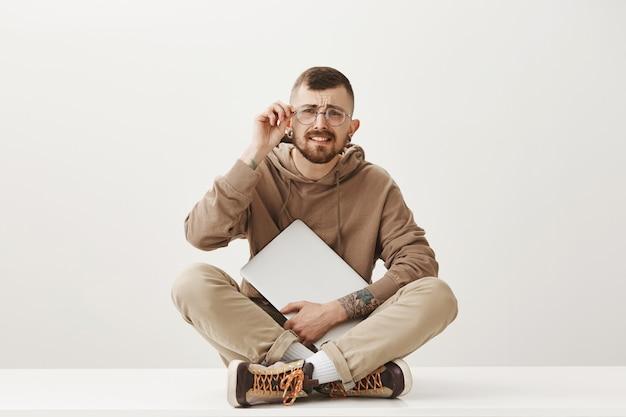 Verward hipster man zit gekruiste benen met laptop, zet een bril op om te zien