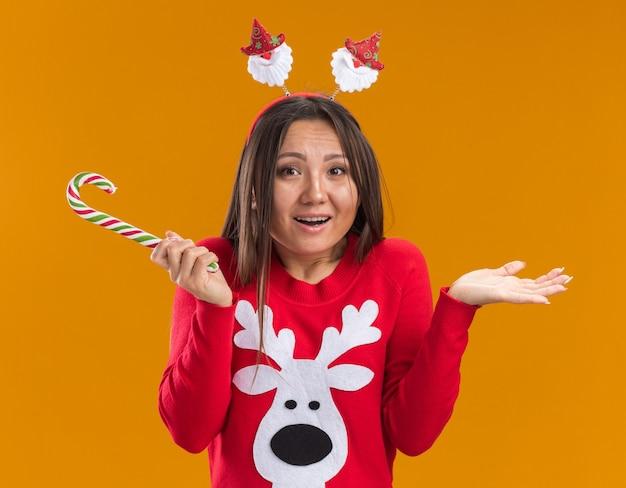 Verward jong aziatisch meisje die de hoepel van het kerstmishaar met sweater dragen die kerstmissuikergoed verspreiden die handen op oranje muur worden geïsoleerd
