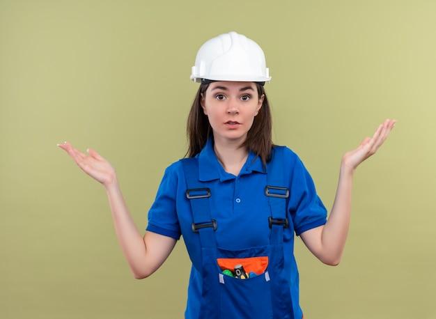 Verward jong bouwersmeisje met witte veiligheidshelm en blauw uniform houdt handen omhoog en kijkt naar camera op geïsoleerde groene achtergrond