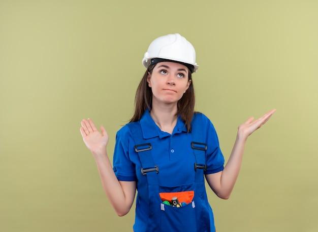 Verward jong bouwersmeisje met witte veiligheidshelm en blauw uniform houdt handen omhoog en kijkt omhoog op geïsoleerde groene achtergrond met exemplaarruimte