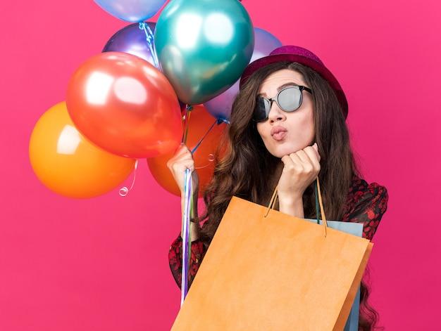 Verward jong feestmeisje met feestmuts en zonnebril met ballonnen en papieren zakken die de hand onder de kin houden en naar de zijkant kijken met getuite lippen geïsoleerd op roze muur
