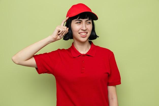 Verward jong kaukasisch bezorgmeisje dat vinger op haar hoofd legt en naar de zijkant kijkt