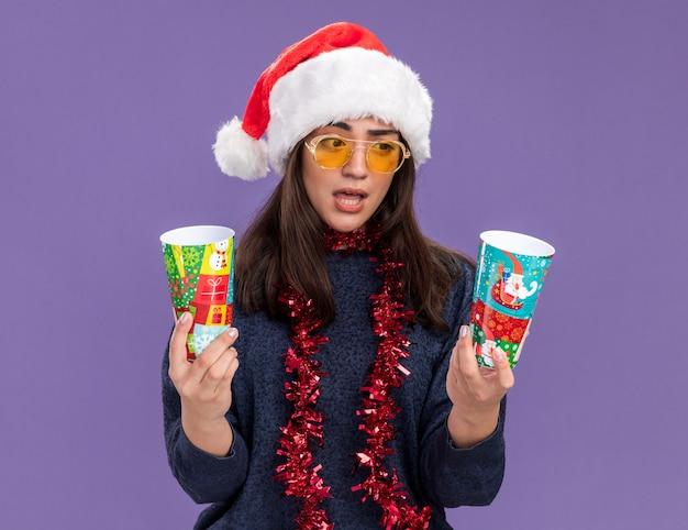 Verward jong kaukasisch meisje in zonnebril met kerstmuts en slinger om nek houdt en kijkt naar papieren bekers geïsoleerd op paarse muur met kopieerruimte
