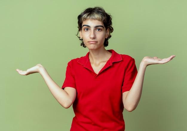 Verward jong kaukasisch meisje met pixiekapsel die lege die handen tonen op olijfgroene achtergrond worden geïsoleerd
