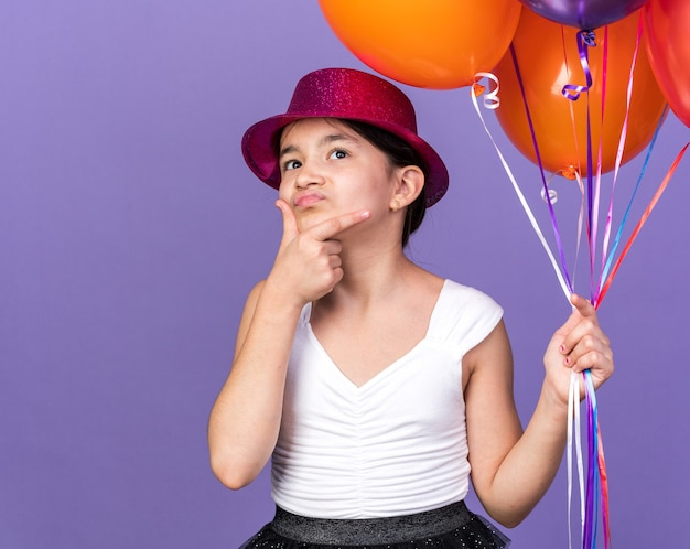 Verward jong kaukasisch meisje met violette feestmuts met helium ballonnen en hand op kin opzoeken geïsoleerd op paarse muur met kopie ruimte