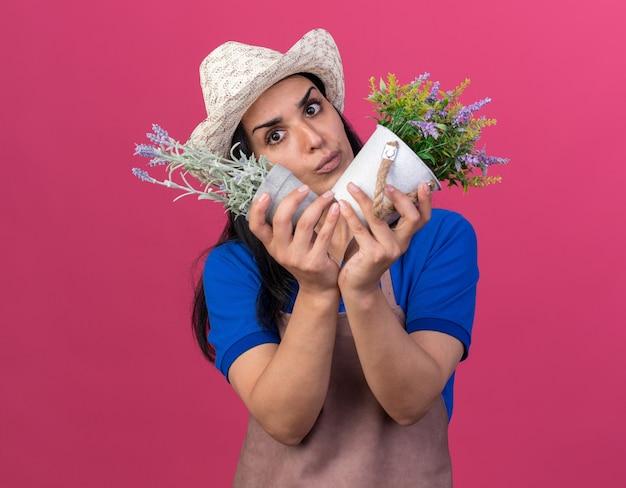 Verward jong kaukasisch tuinmanmeisje met uniform en hoed kijkend naar kant met bloempotten geïsoleerd op roze muur