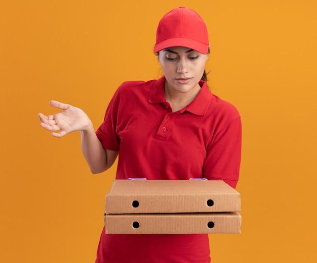 Verward jong leveringsmeisje die eenvormig en glb dragen die en pizzadozen bekijken die hand verspreiden die op oranje muur wordt geïsoleerd