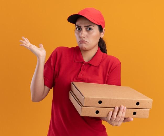 Verward jong leveringsmeisje die eenvormig en glb dragen die pizzadozen houden die hand verspreiden die op oranje muur wordt geïsoleerd