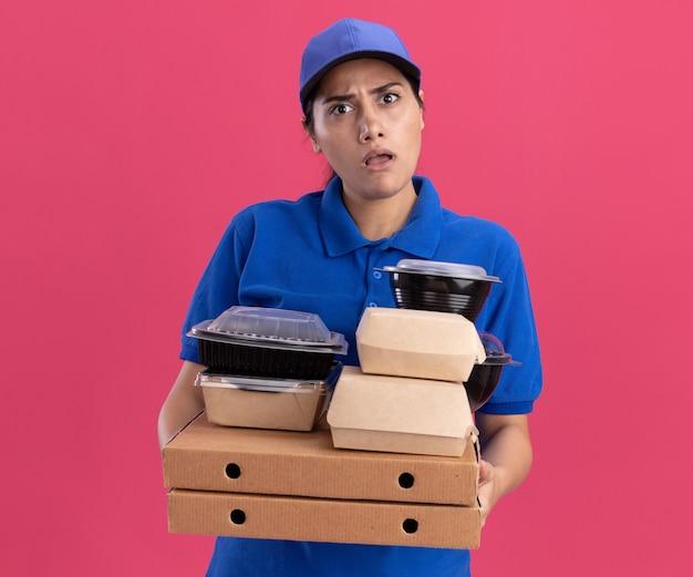 Verward jong leveringsmeisje die eenvormig met glb dragen die voedselcontainers op pizzadozen houden die op roze muur worden geïsoleerd