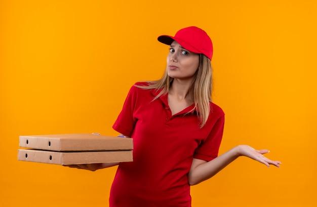 Verward jong leveringsmeisje die rood uniform en pet dragen die pizzadoos houden en uitgespreide hand op oranje muur wordt geïsoleerd